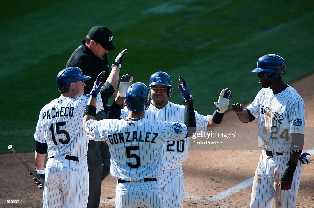 Wilin Rosario #20 of the Colorado Rockies celebrates a three-run home run with teammates Carlos Gonzalez #5 and Dexter Fowler #24, who scored on the play, and Jordan Pacheco #15, who was about to bat in the seventh inning against the San Diego Padres at Coors Field on April 7, 2013 in Denver, Colorado. The Rockies beat the Padres 9-1.