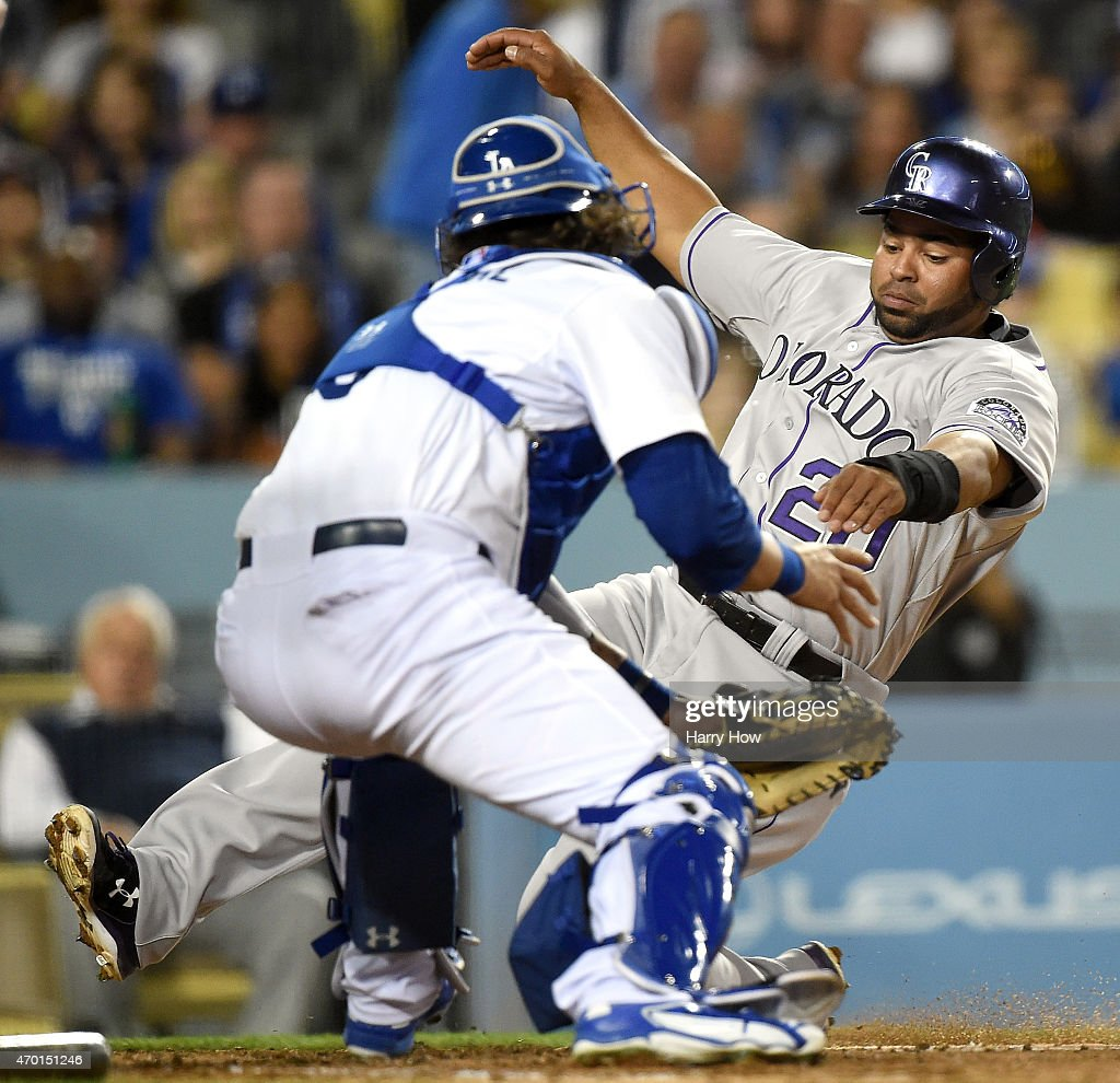 Wilin Rosario #20 of the Colorado Rockies is tagged out at the plate by Yasmani Grandal #9 of the Los Angeles Dodgers during the fourth inning at Dodger Stadium on April 17, 2015 in Los Angeles, California.