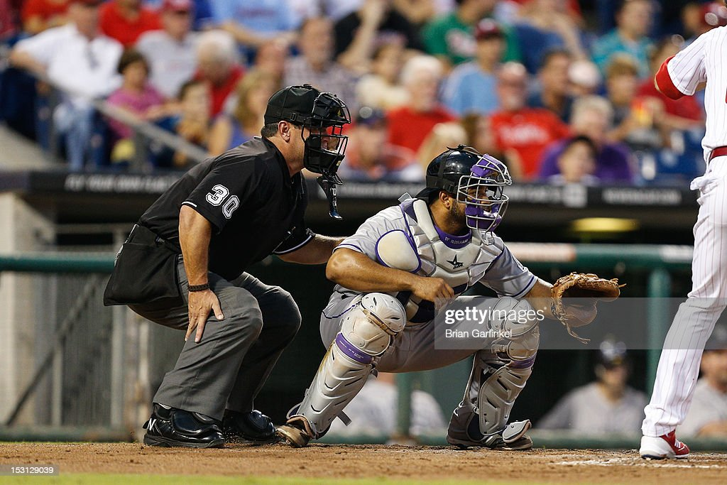 Wilin Rosario of the Colorado Rockies prepares for a pitch with umpire Rob Drake behind the plate during the game against the Philadelphia Phillies...