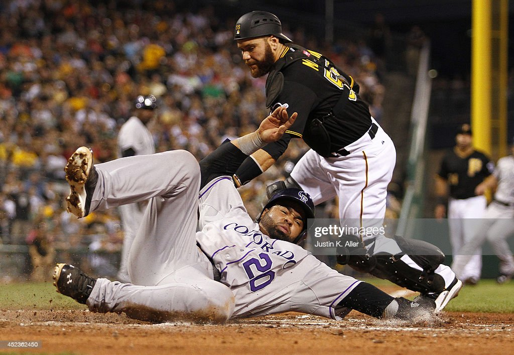 Wilin Rosario #20 of the Colorado Rockies score on a RBI single in the sixth inning against Russell Martin #55 of the Pittsburgh Pirates during the game at PNC Park July 18, 2014 in Pittsburgh, Pennsylvania.