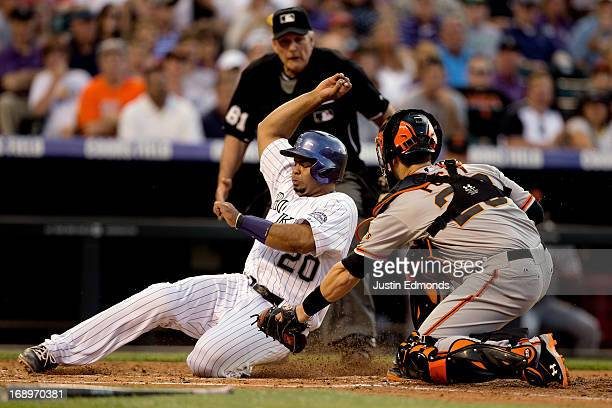 Wilin Rosario of the Colorado Rockies scores before catcher Buster Posey of the San Francisco Giants can apply the tag as home plate umpire Bob...