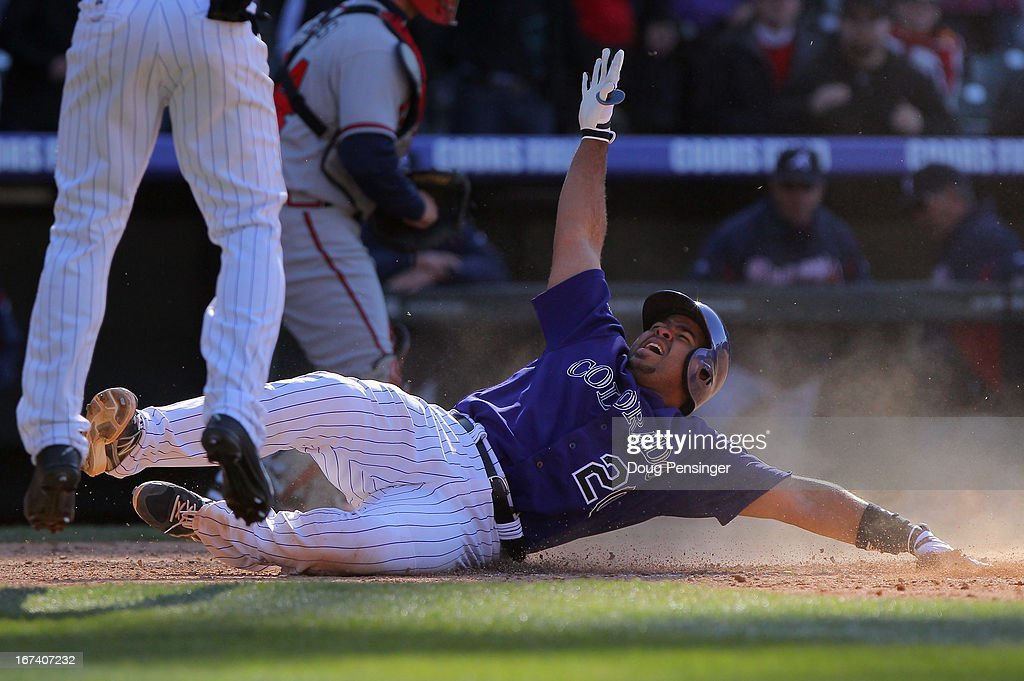<a gi-track='captionPersonalityLinkClicked' href=/galleries/search?phrase=Wilin+Rosario&family=editorial&specificpeople=5734314 ng-click='$event.stopPropagation()'>Wilin Rosario</a> #20 of the Colorado Rockies slides home with the winning run and celebrates with <a gi-track='captionPersonalityLinkClicked' href=/galleries/search?phrase=Jonathan+Herrera&family=editorial&specificpeople=4175178 ng-click='$event.stopPropagation()'>Jonathan Herrera</a> #18 of the Colorado Rockies on a single by Yorvit Torrealba #8 of the Colorado Rockies off of Luis Ayala #20 of the Atlanta Braves in the bottom of the 12th inning at Coors Field on April 24, 2013 in Denver, Colorado. The Rockies defeated the Braves 6-5 in 12 innings.