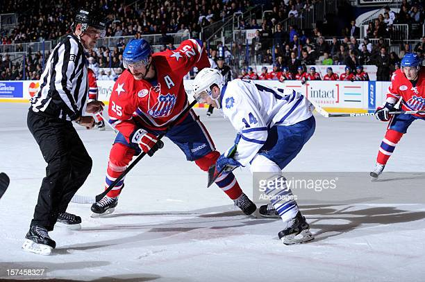 Will Acton of the Toronto Marlies takes the draw against Mark Mancari of the Rochester Americans in front of linseman Kevin Hastings during AHL game...