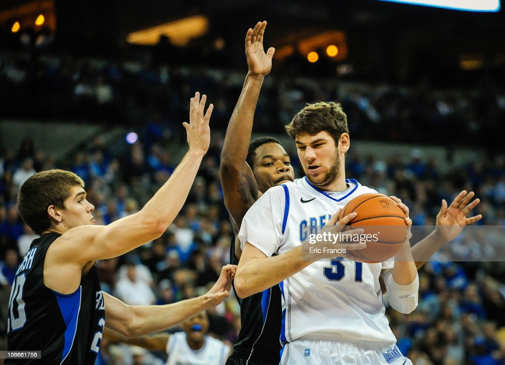 Will Artino #31 of the Creighton Bluejays is guarded by Ryan McTavish #20 and Joshua Clyburn #1 of the Presbyterian Blue Hose during their game at CenturyLink Center on November 18, 2012 in Omaha, Nebraska.