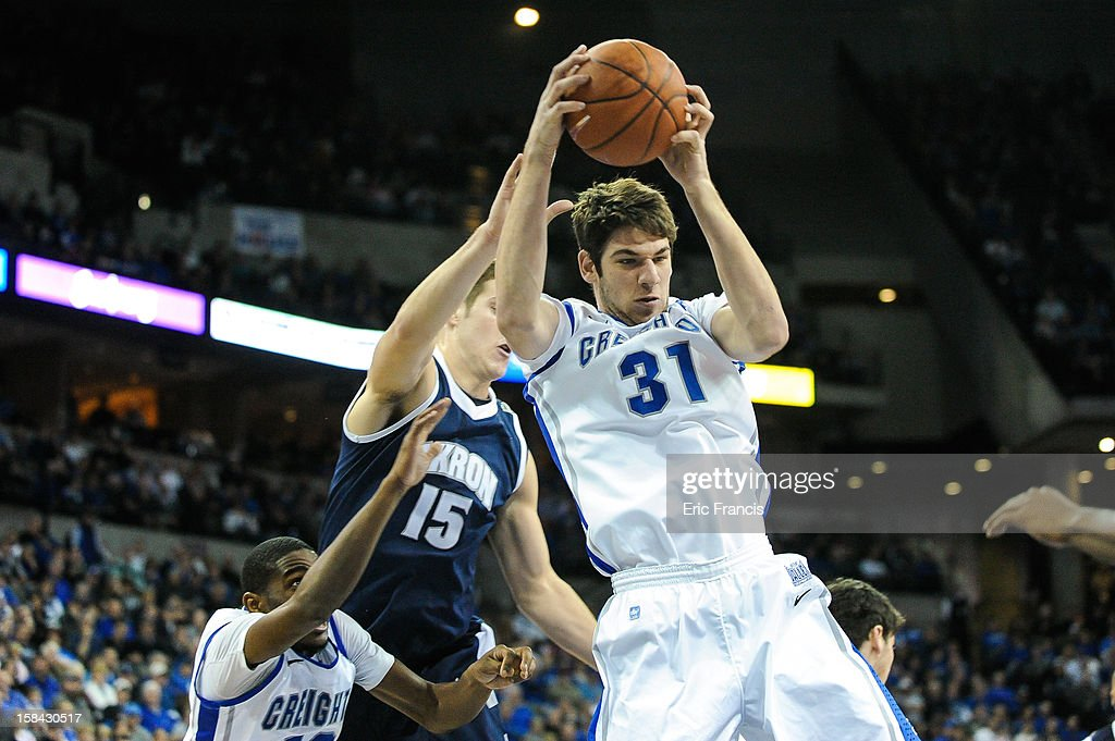 Will Artino #31 of the Creighton Bluejays pulls in a rebound over Jake Kretzer #15 of the Akron Zips during their game at the CenturyLink Center on December 9, 2012 in Omaha, Nebraska.
