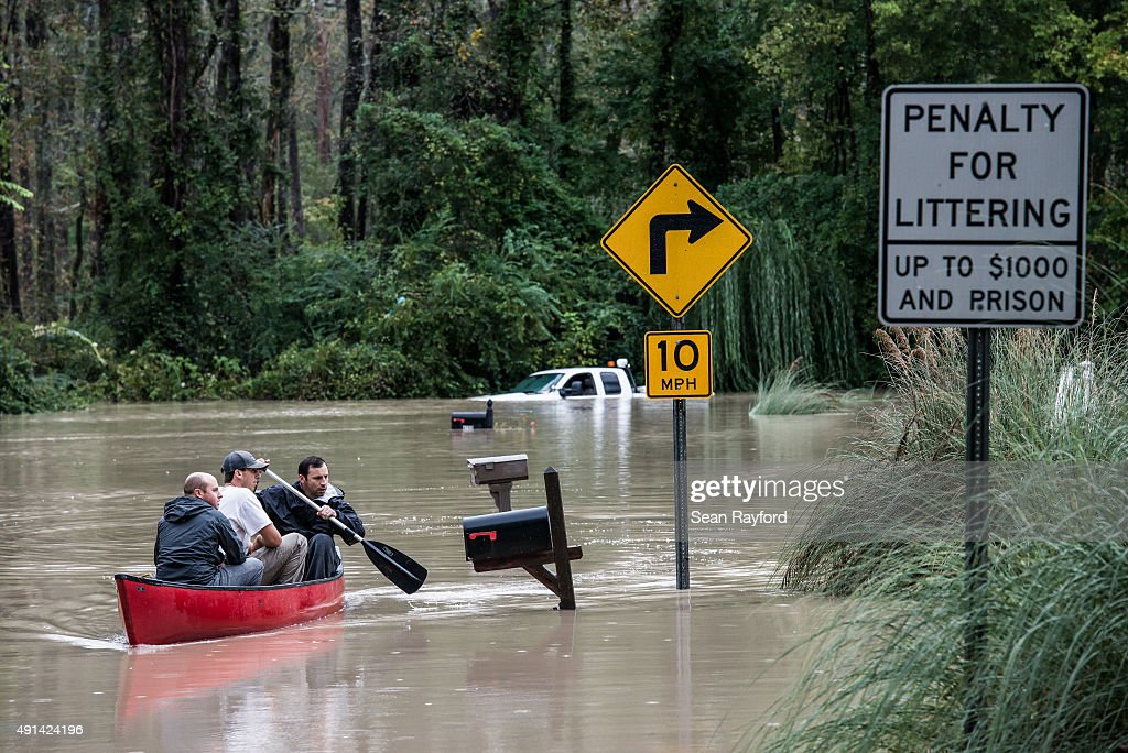 Will Brennan Matt Talley and Tyler Bahnmuller take a canoe to investigate their homes following flooding in the area October 5 2015 in Columbia South...