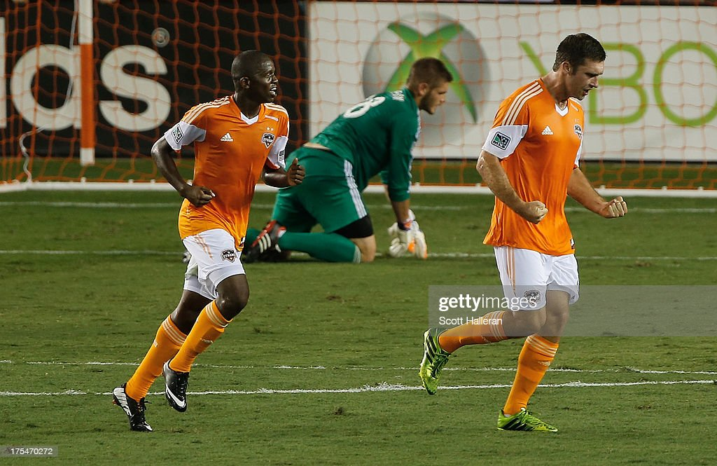 Will Bruin #12 (C) and Boniek Garcia #27 of the Houston Dynamo celebrate after Bruin scored a first half goal past Matt Lampson #28 of the Columbus Crew at BBVA Compass Stadium on August 3, 2013 in Houston, Texas.