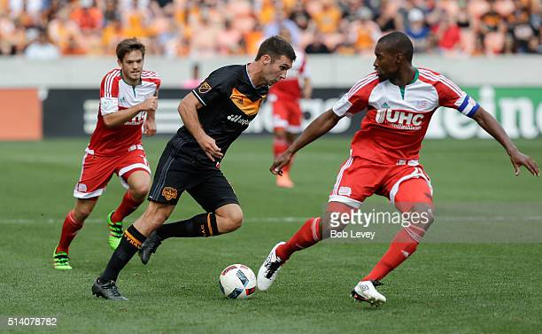 Will Bruin of Houston Dynamo looks to drive by Darrius Barnes of New England Revolution at BBVA Compass Stadium on March 6 2016 in Houston Texas