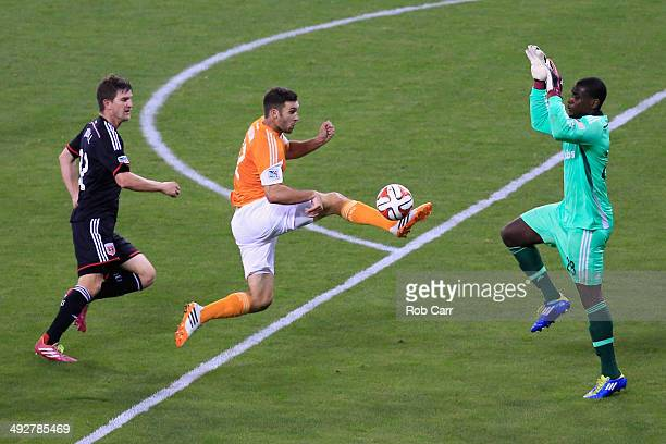 Will Bruin of Houston Dynamo moves the ball past Bobby Boswell and goalie Bill Hamid of DC United during the second half at RFK Stadium on May 21...