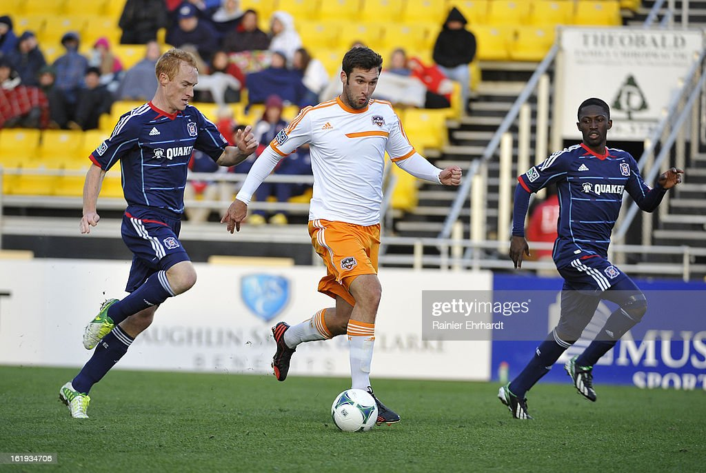 Will Bruin #12 of the Houston Dynamo battles for the ball against Jeff Larentowicz #20 of the Chicago Fire during the first half of their game at Blackbaud Stadium on February 16, 2013 in Charleston, South Carolina.