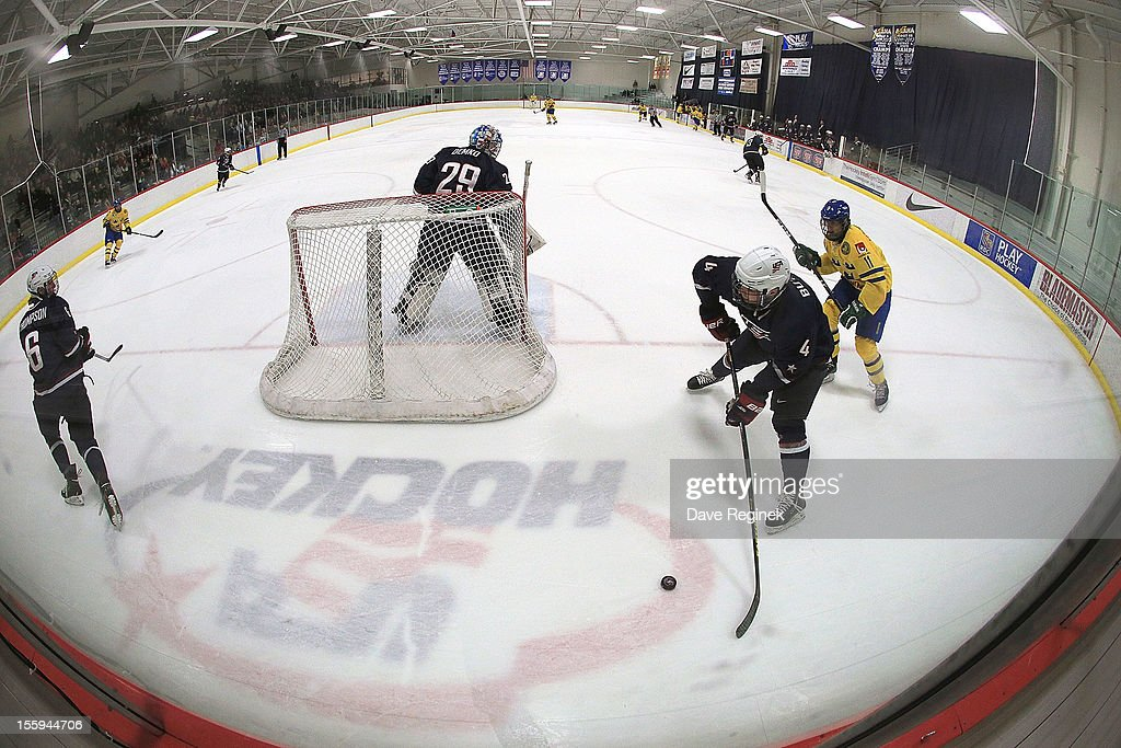 Will Butcher and Keaton Thompson of the USA skate behind the net as Alexander Henriksson of Sweden forechecks during the U18 Four Nations Cup on...