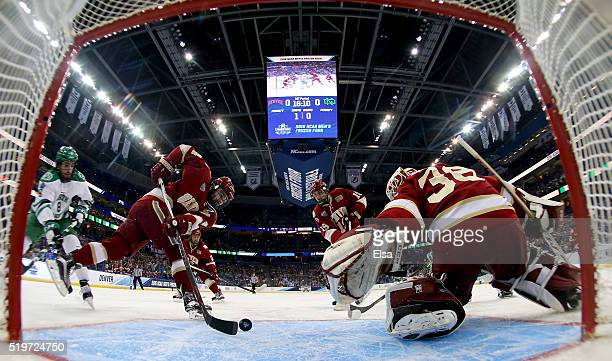 Will Butcher of the Denver Pioneers clears the puck for teammate Tanner Jaillet in the first period against the North Dakota Fighting Hawks during...