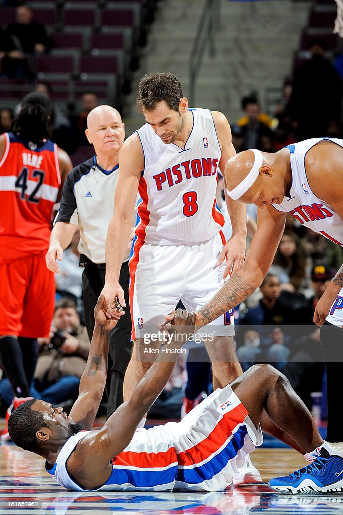 Will Bynum #12 of the Detroit Pistons is helped up by teammates Jose Calderon #8 and Charlie Villanueva #31 during a game against the Washington Wizards on February 13, 2013 at The Palace of Auburn Hills in Auburn Hills, Michigan.