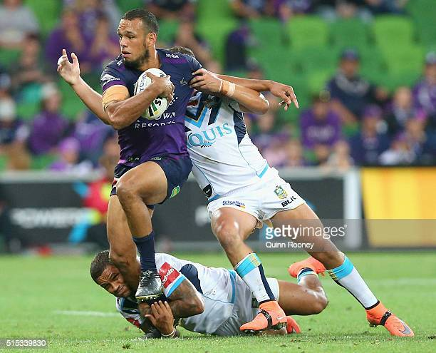 Will Chambers of the Storm breaks through a tackle by Josh Hoffman and Ashley Taylor of the Titans during the round two NRL match between the...