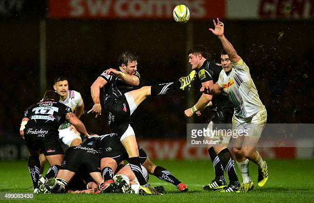 Will Chudley of Exeter Chiefs puts in a box kick under pressure from Nick Easter of Harlequins during the Aviva Premiership match between Exeter...