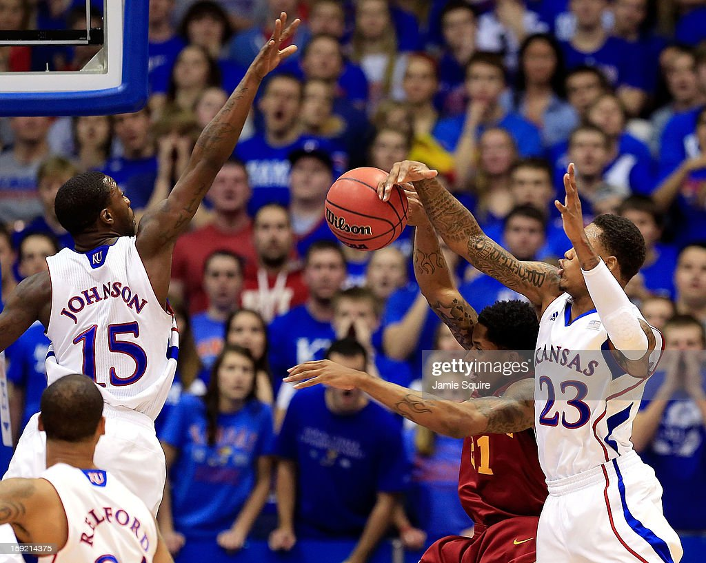 Will Clyburn #21 of the Iowa State Cyclones tries to shoot as Elijah Johnson #15 and Ben McLemore #23 of the Kansas Jayhawks defend during the game at Allen Fieldhouse on January 9, 2013 in Lawrence, Kansas.