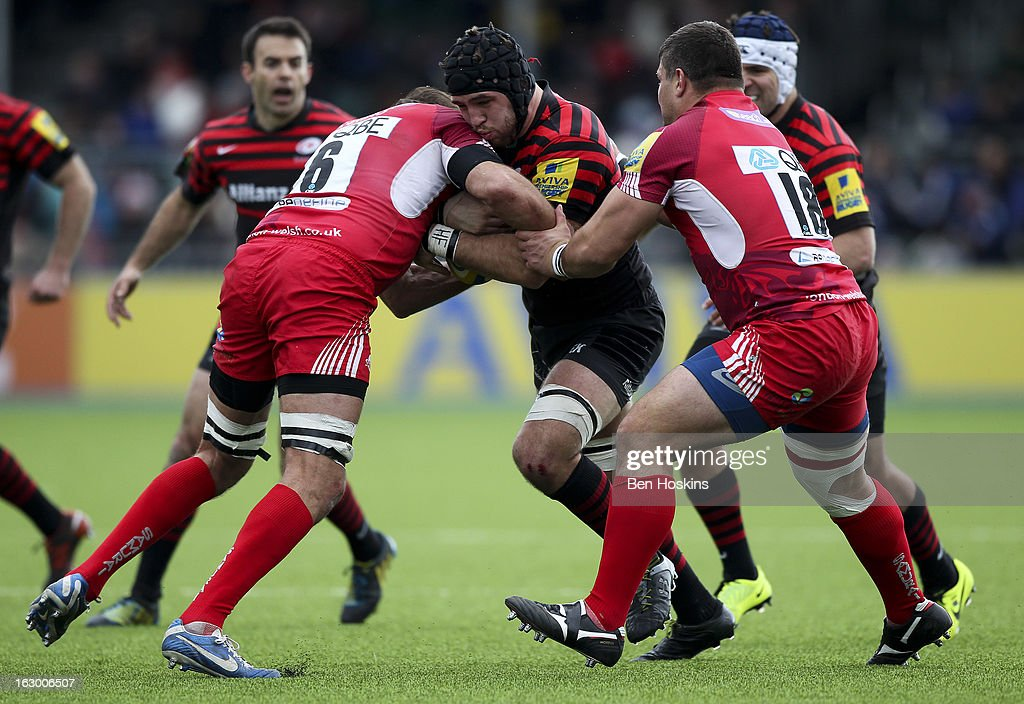 Will Fraser of Saracens is tackled by Julio Cabello Farias (L) and Paulica Ion (R) of London Welsh during the Aviva Premiership match between Saracens and London Welsh at Allianz Park on March 03, 2013 in Barnet, England.