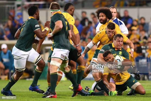 Will Genia of Australia gets tackled by Coenraad Oosthuizen of South Africa during The Rugby Championship match between the Australian Wallabies and...
