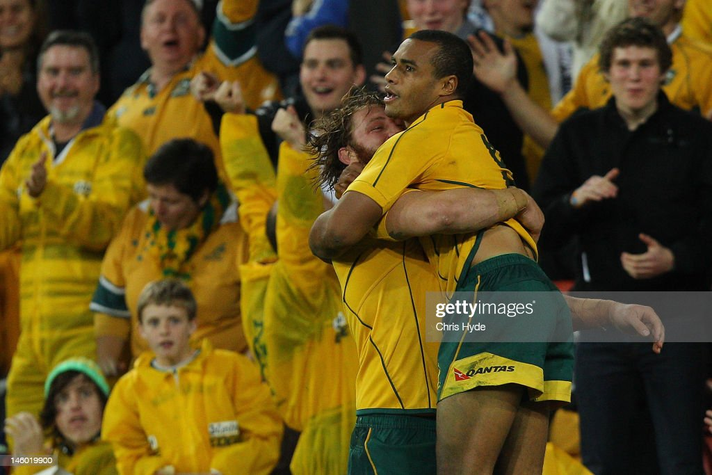 <a gi-track='captionPersonalityLinkClicked' href=/galleries/search?phrase=Will+Genia&family=editorial&specificpeople=4110822 ng-click='$event.stopPropagation()'>Will Genia</a> of the Wallabies celebrates with team mate <a gi-track='captionPersonalityLinkClicked' href=/galleries/search?phrase=Scott+Higginbotham&family=editorial&specificpeople=2303432 ng-click='$event.stopPropagation()'>Scott Higginbotham</a> after scoring a try during the international test match between the Australian Wallabies and Wales at Suncorp Stadium on June 9, 2012 in Brisbane, Australia.