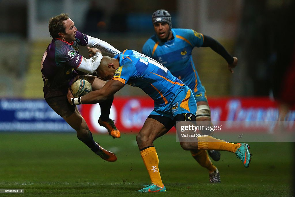 Will Harries (L) of Newport Gwent Dragons holds onto <a gi-track='captionPersonalityLinkClicked' href=/galleries/search?phrase=Tom+Varndell&family=editorial&specificpeople=561563 ng-click='$event.stopPropagation()'>Tom Varndell</a> (R) of London Wasps during the Amlin Challenge Cup Pool Three match between Newport Gwent Dragons and London Wasps at Rodney Parade on January 17, 2013 in Newport, Wales.