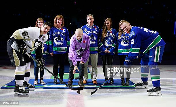 Will Heine drops the puck for Sidney Crosby of the Pittsburgh Penguins and Henrik Sedin of the Vancouver Canucks on Hockey Fights Cancer night before...