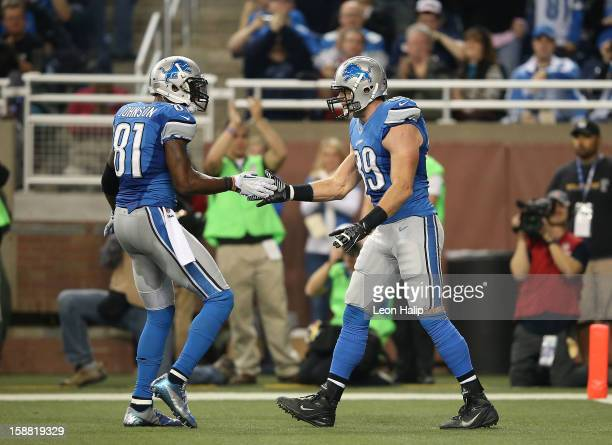 Will Heller of the Detroit Lions celebrates with teammate Calvin Johnson after scoring on a short pass from Matthew Stafford during the third quarter...