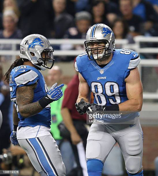 Will Heller of the Detroit Lions celebrates with teammate Mikel Leshoure after scoring on a short pass from Matthew Stafford during the third quarter...