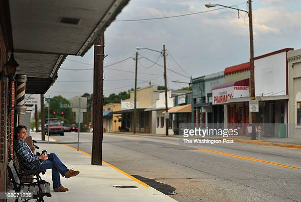 Will Helms left sits on a bench along Main St on Saturday April 27 2013 in Loganville GA In January Loganville GA resident Melinda Herman was home...