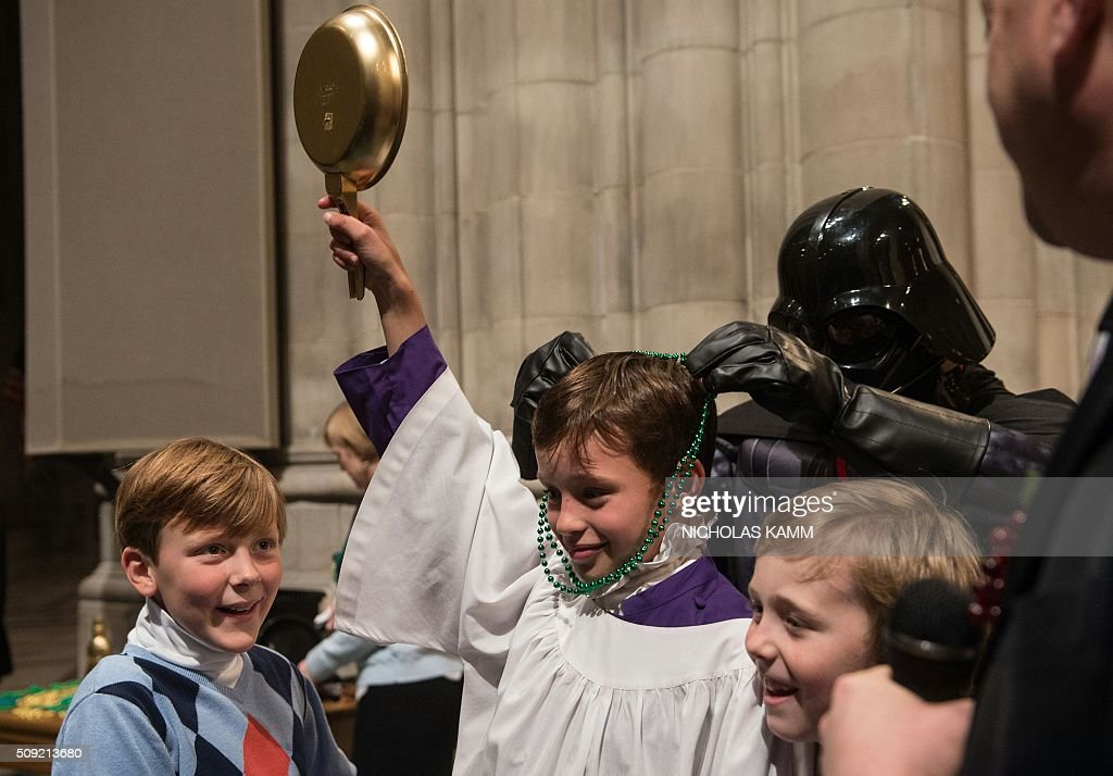 Will Hohlt holds the Golden Skillet after winning the Shrove Tuesday Pancake Race at the National Cathedral in Washington, DC, on February 9, 2016. Shrove Tuesday, also known as Mardi Gras, precedes Ash Wednesday, the first day of Lent. / AFP / Nicholas Kamm