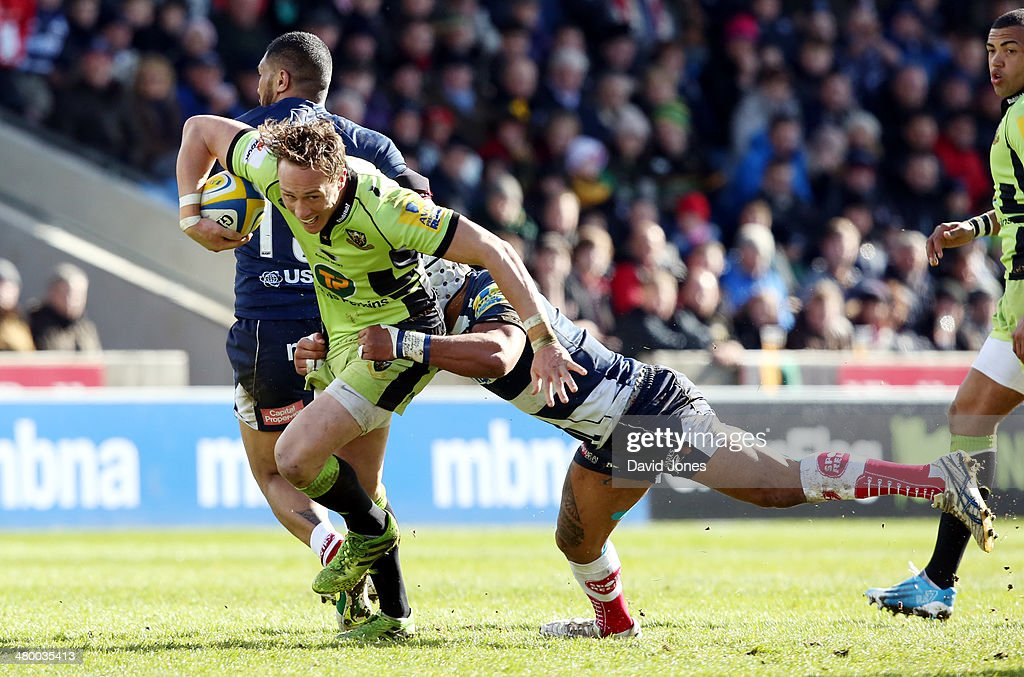 Will Hooley of Northampton Saints is tackled by Sam Tuitupou of Sale Sharks during the Aviva Premiership match between Sale Sharks and Northampton Saints at A J Bell Stadium on March 22, 2014 in Salford, England