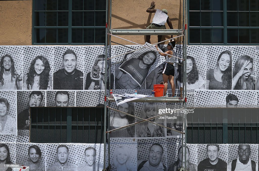 Will Hopkins (top) and Sarah Hamideh use adhesive to attach pictures to the wall of the Freedom Tower as they hang the 'Inside Out 11M' project on August 31, 2013 in Miami, Florida. The public art project puts a face on immigration reform by creating a massive mosaic of portraits taken on site, printed immediately and pasted on the Freedom Tower at Miami-Dade College.