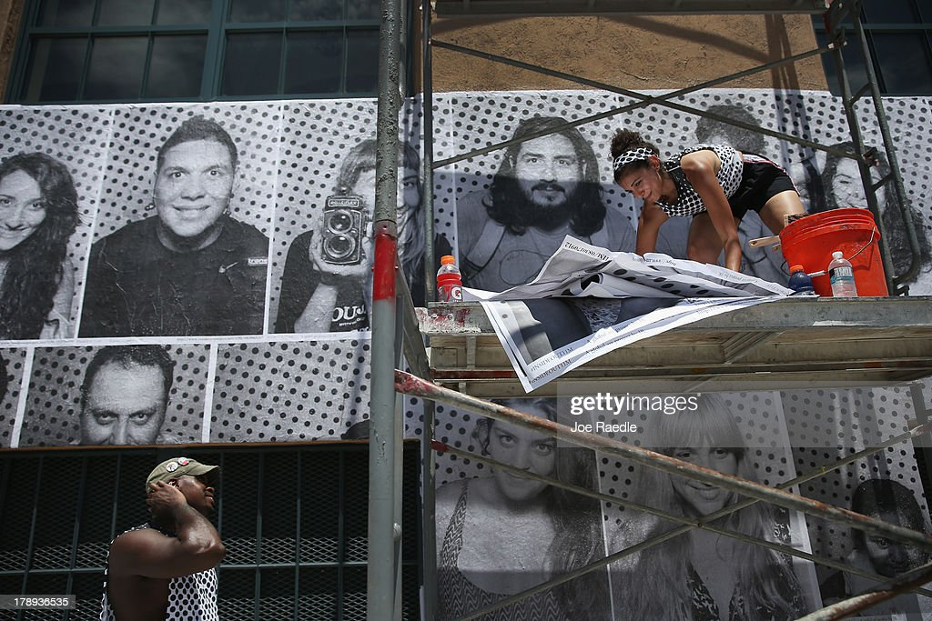 Will Hopkins (L) and Sarah Hamideh use adhesive to attach pictures to the wall of the Freedom Tower as they hang the 'Inside Out 11M' project on August 31, 2013 in Miami, Florida. The public art project puts a face on immigration reform by creating a massive mosaic of portraits taken on site, printed immediately and pasted on the Freedom Tower at Miami-Dade College.