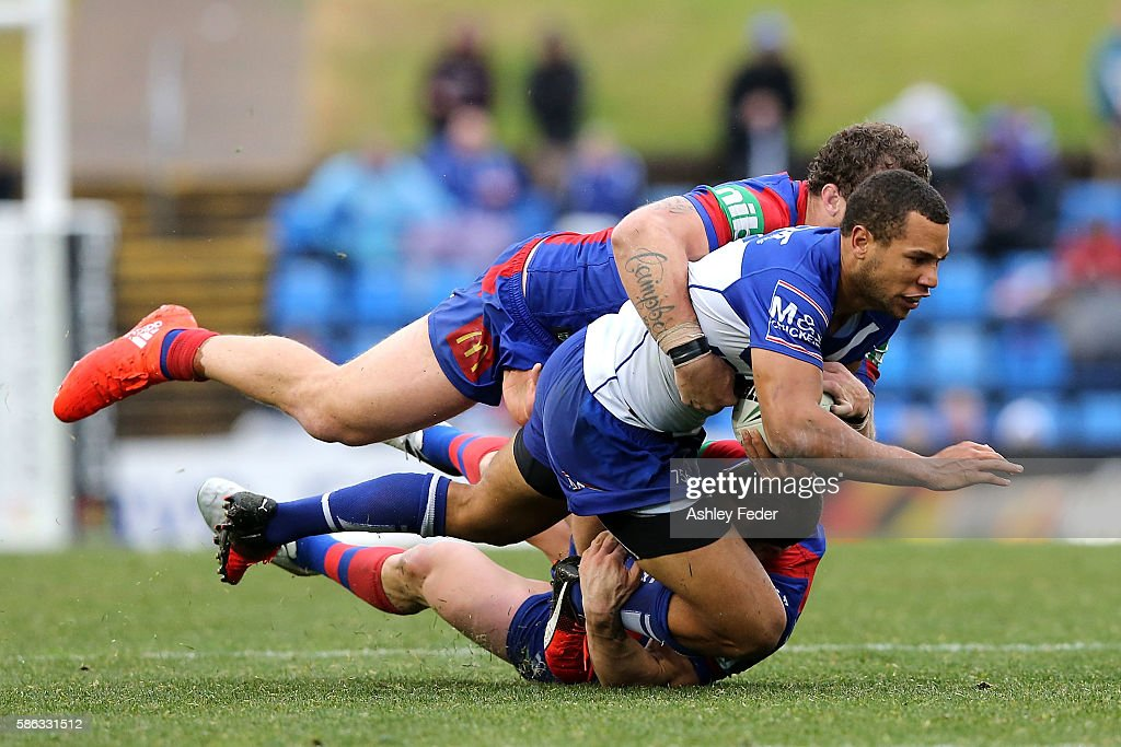 Will Hopoate of the Bulldogs is tackled by the Knights defence during the round 22 NRL match between the Newcastle Knights and the Canterbury Bulldogs at Hunter Stadium on August 6, 2016 in Newcastle, Australia.