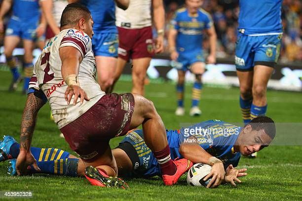 Will Hopoate of the Eels scores a try under pressure from Jorge Taufua of the Sea Eagles during the round 24 NRL match between the Parramatta Eels...