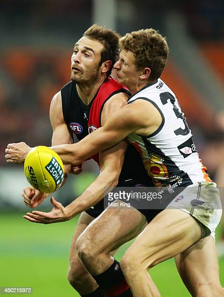 Will HoskinElliott of the Giants competes for the ball against Jobe Watson of the Bombers during the round 12 AFL match between the Greater Western...