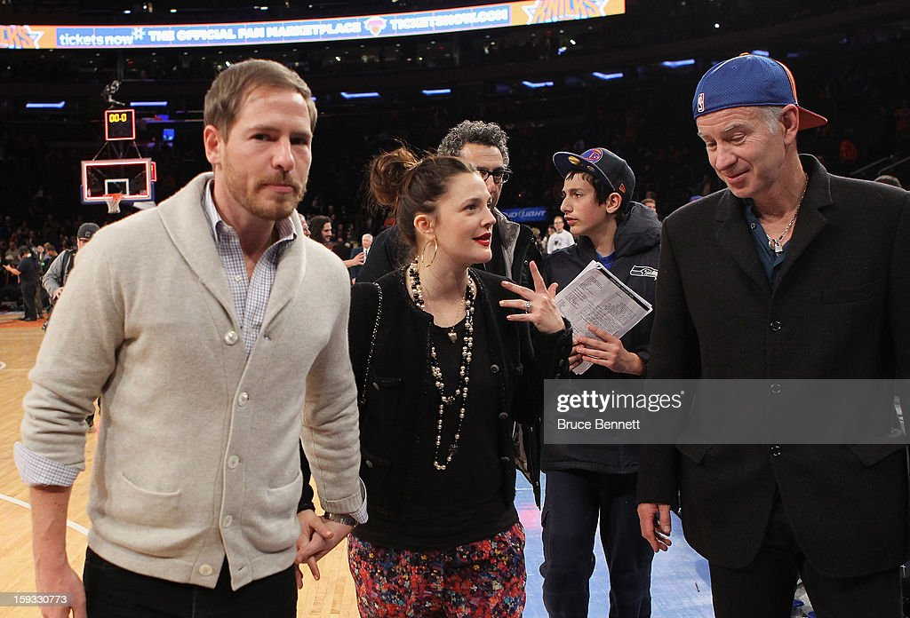Will Kopelman, Drew Barrymore and John McEnroe leave the court following the New York Knicks 108-101 loss to the Chicago Bulls at Madison Square Garden on January 11, 2013 in New York City.