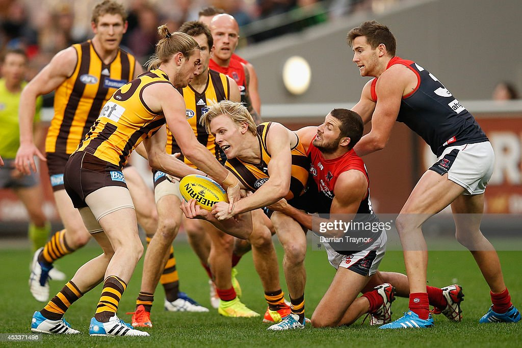 Will Langford of the Hawks handballs as Colin Garland of the Demons tackles him during the round 20 AFL match between the Hawthorn Hawks and the Melbourne Demons at Melbourne Cricket Ground on August 9, 2014 in Melbourne, Australia.