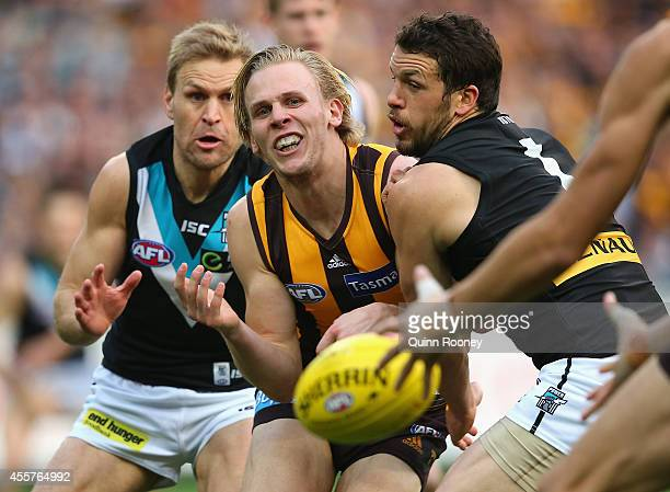 Will Langford of the Hawks handballs whilst being tackled by Kane Cornes and Travis Boak of the Power during the AFL 2nd Preliminary Final match...