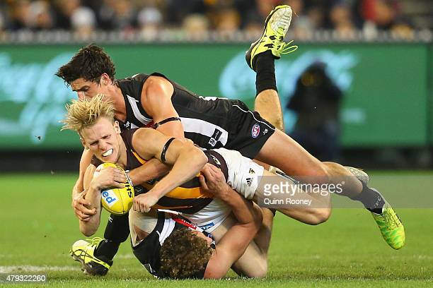 Will Langford of the hawks is tackled by Scott Pendlebury of the Magpies during the round 14 AFL match between the Collingwood Magpies and the...