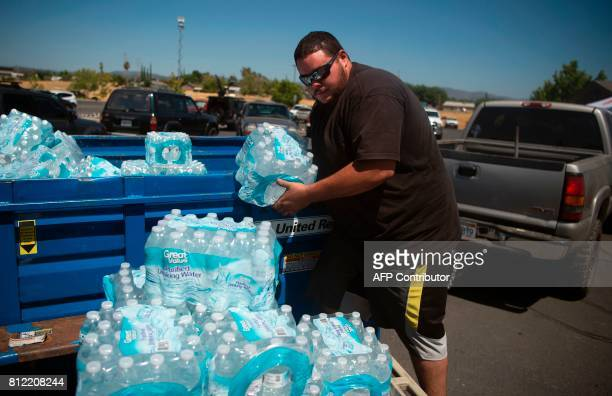 Will Lemire unloads 70 cases of water that he purchased at Walmart as a donation for evacuees at an evacuation center in Oroville California on July...