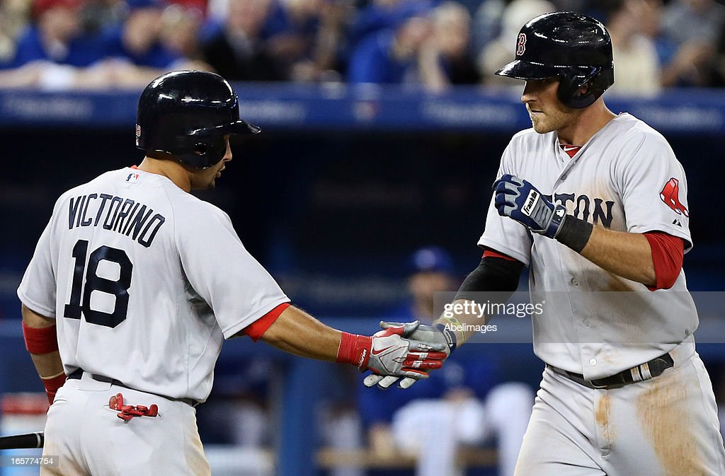 Will Middlebrooks #16 and Shane Victorino #18 of the Boston Red Sox celebrate Will Middlebrooks solo home run in the 9th inning against the Toronto Blue Jays during MLB action at the Rogers Centre April 5, 2013 in Toronto, Ontario, Canada.