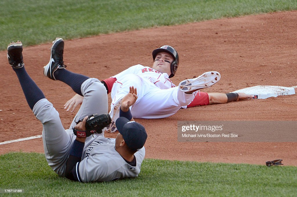 Will Middlebrooks #16 of the Boston Red Sox and Alex Rodriguez #13 of the New York Yankees react after colliding on a fielders choice during the fourth inning on August 17, 2013 at Fenway Park in Boston Massachusetts.