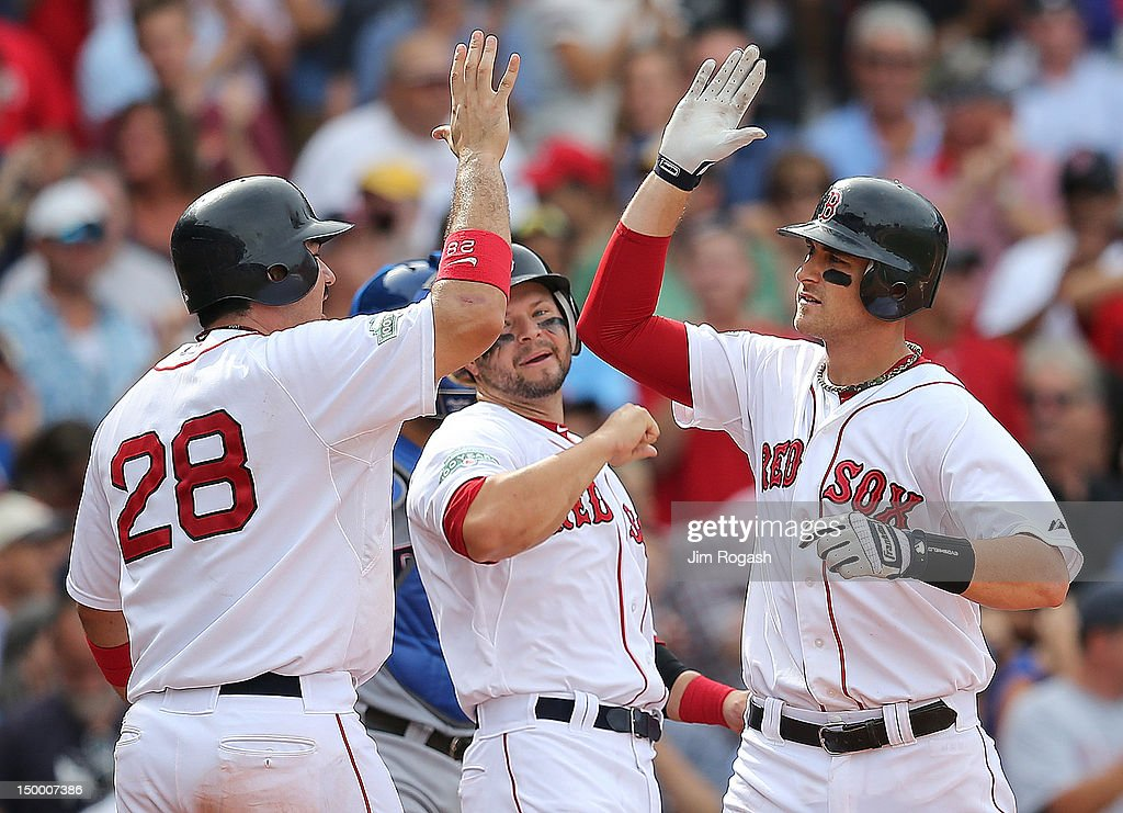 Will Middlebrooks #64 of the Boston Red Sox celebrates his home run with Adrian Gonzalez #28 and Cody Ross #7, who were on base, in the seventh inning against the Boston Red Sox at Fenway Park August 8, 2012 in Boston, Massachusetts.