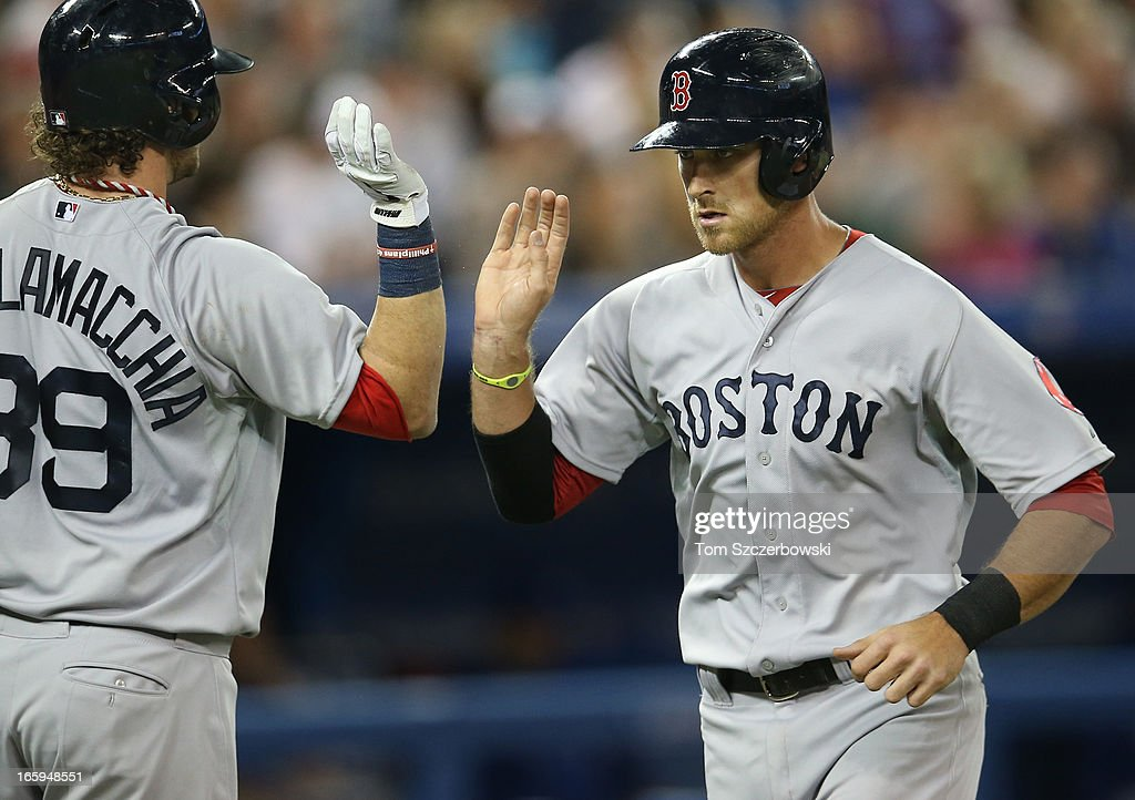 Will Middlebrooks #16 of the Boston Red Sox is congratulated by Saltalamacchia #39 after scoring a run in the third inning on a sacrifice fly during MLB game action against the Toronto Blue Jays on April 7, 2013 at Rogers Centre in Toronto, Ontario, Canada.