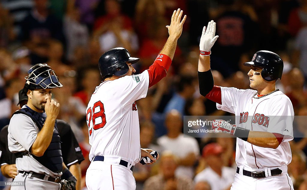 Will Middlebrooks #64 of the Boston Red Sox is congratulated by teammate Adrian Gonzalez #28 after hitting a two-run home run against the Detroit Tigers in the 8th inning during the game on July 30, 2012 at Fenway Park in Boston, Massachusetts.