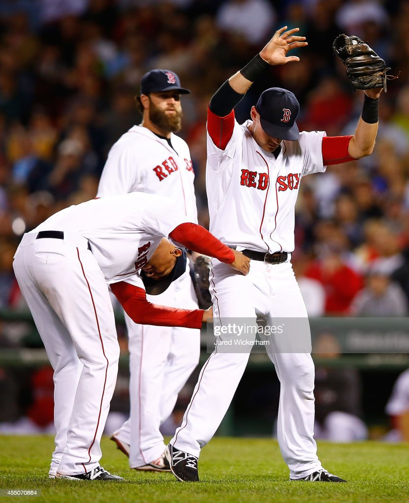 <a gi-track='captionPersonalityLinkClicked' href=/galleries/search?phrase=Will+Middlebrooks&family=editorial&specificpeople=7934204 ng-click='$event.stopPropagation()'>Will Middlebrooks</a> #16 of the Boston Red Sox is grabbed by the waist by teammate <a gi-track='captionPersonalityLinkClicked' href=/galleries/search?phrase=Xander+Bogaerts&family=editorial&specificpeople=9461957 ng-click='$event.stopPropagation()'>Xander Bogaerts</a> #2 after catching a fly ball in the infield against the Baltimore Orioles during the game at Fenway Park on September 9, 2014 in Boston, Massachusetts.