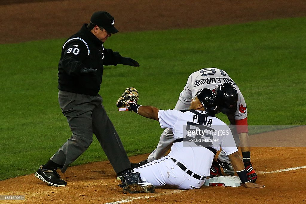 Will Middlebrooks of the Boston Red Sox slides into thid base safe against Brayan Pena of the Detroit Tigers in the ninth inning as third base umpire...