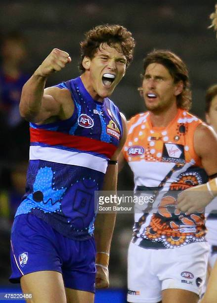 Will Minson of the Bulldogs celebrates after kicking a goal as Ryan Griffen of the Giants looks on during the round nine AFL match between the...