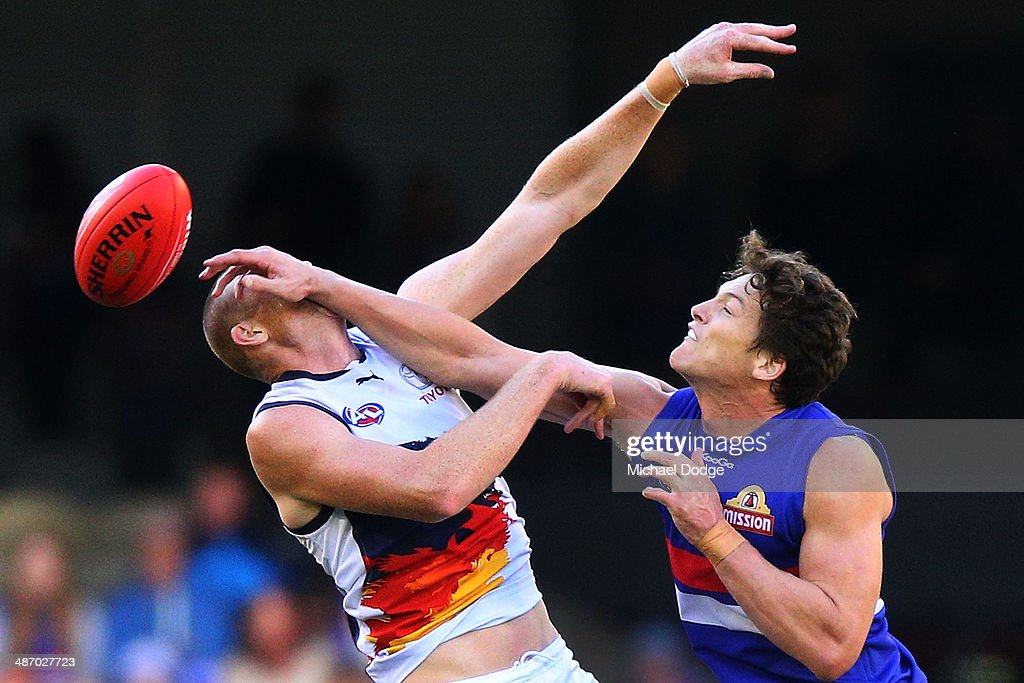 Will Minson (R) of the Bulldogs hits Sam Jacobs of the Crows in the face during a ruck contest during the round six AFL match between the Western Bulldogs and the Adelaide Crows at Etihad Stadium on April 27, 2014 in Melbourne, Australia.