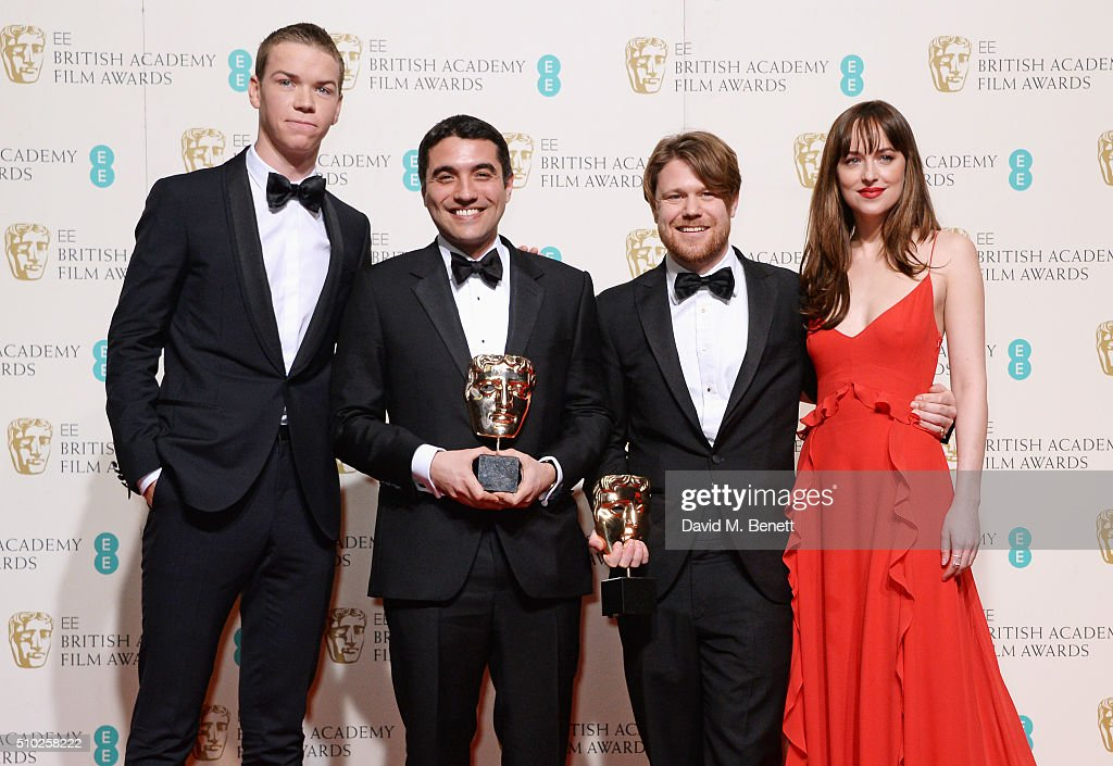 Will Poulter (L) and Dakota Johnson pose with Naji Abu Nowar (2L) and Rupert Lloyd, winners of the Outstanding Debut award for 'Theeb', in the winners room at the EE British Academy Film Awards at The Royal Opera House on February 14, 2016 in London, England.